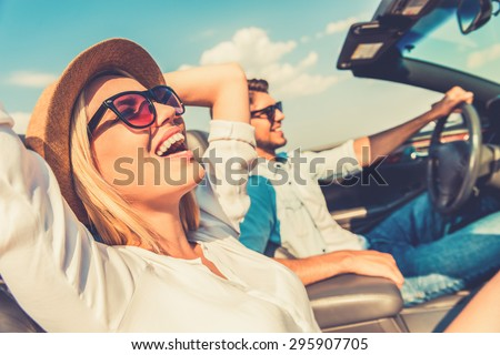 Freedom of the open road. Side view of joyful young woman relaxing on the front seat while her boyfriend sitting near and driving their convertible  - stock photo