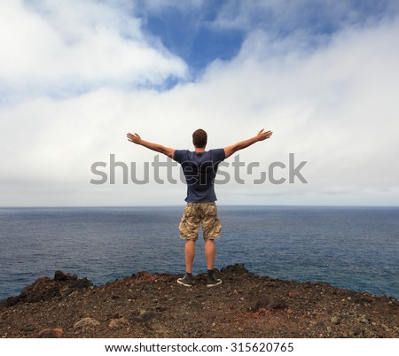 Freedom or nature lover concept - man with arms raised at seashore - stock photo