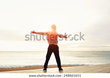 Freedom, relax and harmony in nature, Rear view of a young guy with his arms outstretched at the seaside standing next to the sea, happiness emotional concept - stock photo