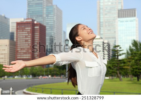 Freedom success businesswoman - Happy free Asian mixed race business woman in Japanese downtown Tokyo city skyline. Carefree young adult arms open up in the sky, Japan. - stock photo
