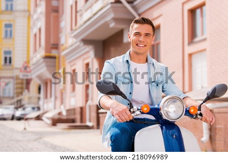 Freedom to go everywhere. Handsome young man riding scooter along the street and smiling  - stock photo