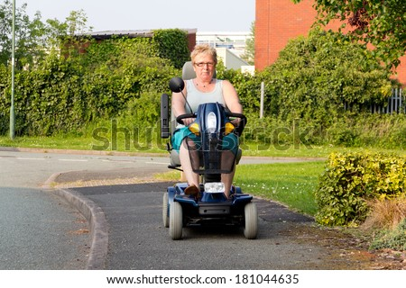 Freedom to roam-Lady ride mobility scooter along pavement on summers day - stock photo