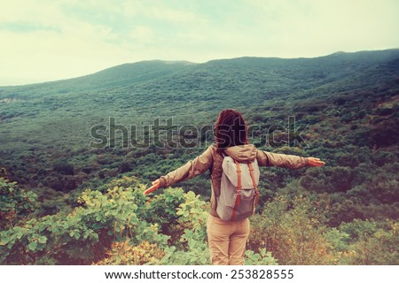 Freedom traveler woman standing with raised arms and enjoying a beautiful nature. Image with instagram filter - stock photo