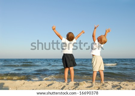 Freedom. Two boys on the beach with arms raised