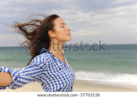 freedom: woman enjoying the wind and the sea - stock photo