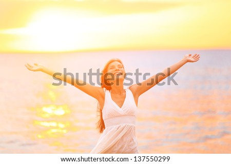 Freedom woman happy and free open arms on beach at sunny sunset. Beautiful joyful elated woman looking up smiling by the ocean during summer holidays vacation. Pretty multiracial Asian Caucasian girl. - stock photo