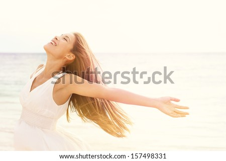 Freedom woman in free happiness bliss on beach. Smiling happy multicultural female model in white summer dress enjoying serene ocean nature during travel holidays vacation outdoors. - stock photo