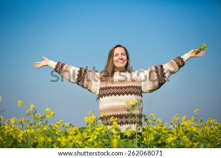 Freedom woman in free happiness bliss on yellow field and blue sky. Smiling happy female model in knitted sweater enjoying nature during travel holidays vacation outdoors - stock photo