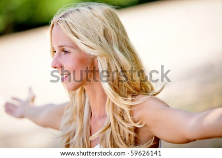 Freedom woman outdoors with her arms opened - stock photo