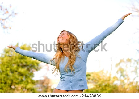 freedom woman smiling outdoors in a park with arms open - stock photo