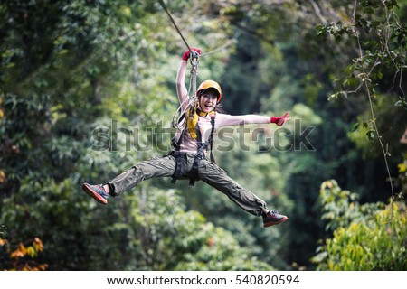 Freedom Woman Tourist Wearing Casual Clothing On Zip Line Or Canopy Experience In Laos Rainforest