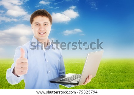 Freedom -Young happy man with laptop in nature - stock photo