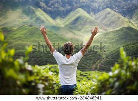 freedom young man with hands up in mountains    - stock photo