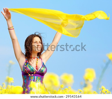 Freedom, young woman with a yellow shawl in rapeseed field - stock photo