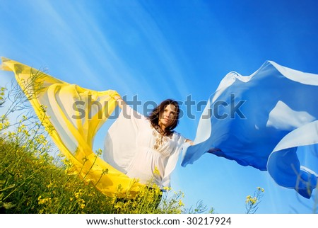 Freedom, young woman with yellow and blue shawl in rapeseed field - stock photo
