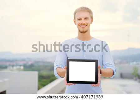 Freelance and technology. Outdoors portrait of handsome young man holding digital tablet, showing screen with copy space. Focus on computer. - stock photo
