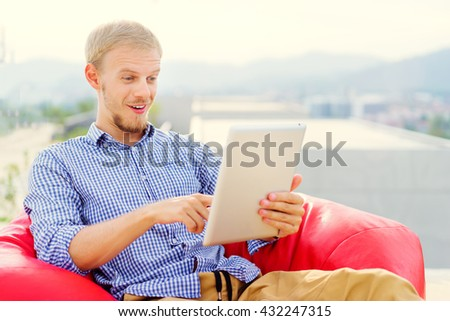 Freelance businessman. Amazed young man using tablet computer while sitting on red bean bag. - stock photo