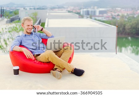 Freelance businessman. Young handsome man working on laptop while sitting on the roof top. - stock photo