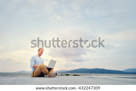 Freelance businessman. Young handsome man working on laptop while sitting on the roof top.