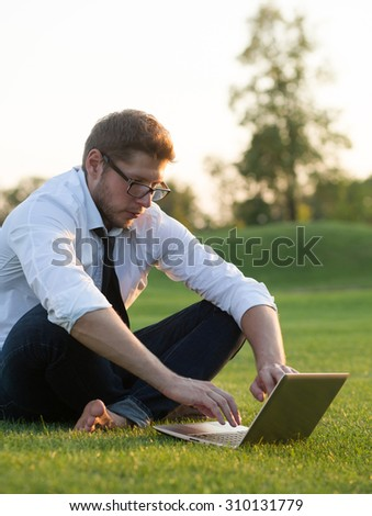 Freelance concept. Close-up of creative man typing on laptop, soft focused, selective focused. Serious man in glasses looking at the notebook's screen. - stock photo
