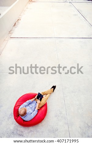 Freelance concept. Top view of young man working on tablet computer sitting on the red bean bag. - stock photo