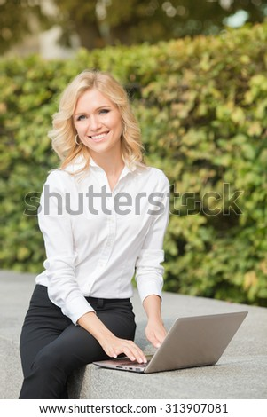 Freelance lady working with laptop computer and smiling for the camera oudoors. Blonde in white shirt and black trousers sitting on brick wall.