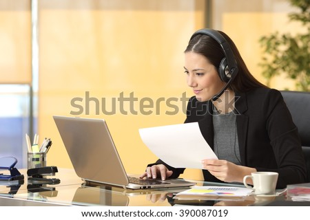 Freelance operator working online with a laptop and headsets and holding a document at office - stock photo