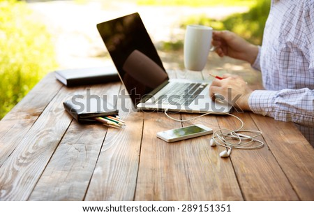 Freelance work. Casual dressed man sitting at wooden desk inside garden working on computer pointing with color pen drinking coffee gadgets dropped around on table side view  - stock photo