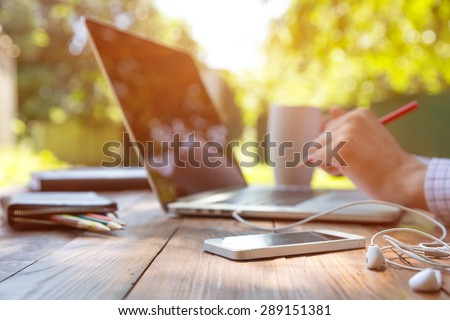 Freelance work. Casual dressed man sitting at wooden desk inside garden working on computer pointing with color pen electronic gadgets dropped around on table side view - stock photo