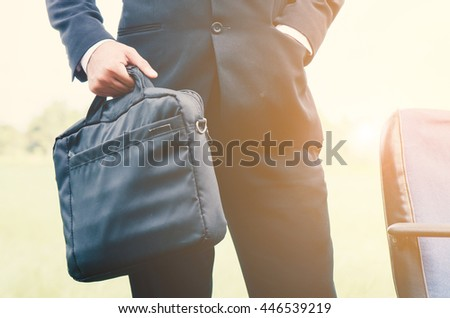 Freelancer. Businessman standing on green meadow with a briefcase. Business concept