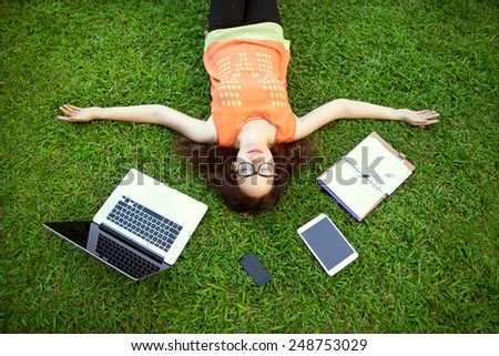 freelancer girl from the device: laptop, tablet, player, notebook, lying on the grass and working  - stock photo
