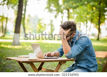 Freelancer hipster man working in the park at the table. Exhausted man searching something ib the Internet using his laptop computer. - stock photo