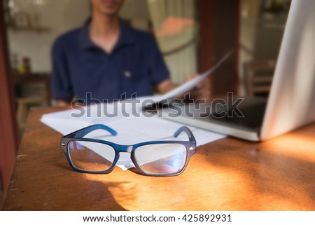 freelancer needs workstation with laptop computer,glasses, business graphics in a coffee shop,vintage effect and morning light.  - stock photo