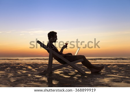 Freelancer sending emails with laptop on tropical beach while traveling