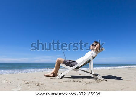 Freelancer working remotely with laptop and resting on sunny tropical beach, sunglasses