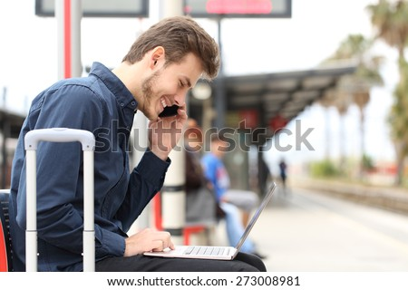 Freelancer working with a laptop and phone in a train station while is waiting for transport - stock photo