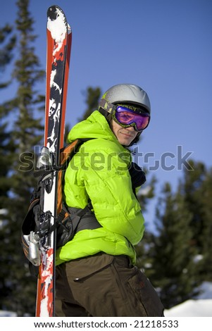 Freeride skier with skis on the backpack - stock photo