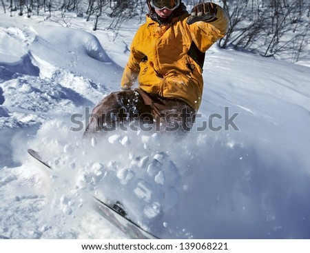 Freerider snowboarder moving down in snow powder - stock photo