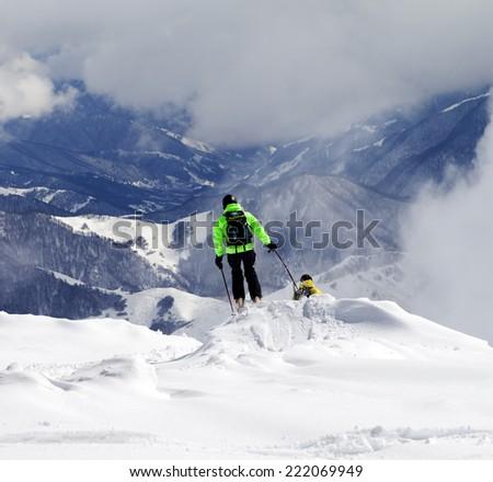 Freeriders on off-piste slope and mountains in haze. Caucasus Mountains, Georgia, ski resort Gudauri.  - stock photo