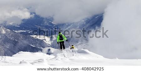 Freeriders on off-piste slope and mountains in mist. Caucasus Mountains, Georgia, region Gudauri. - stock photo