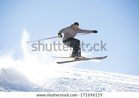 Freestyle ski jumper with crossed skis in snowy mountains - stock photo