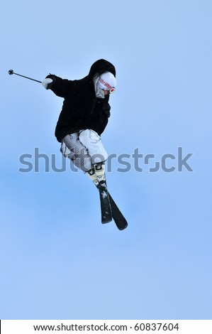freestyle skier in black jacket performing a jump and starting a tele-heli