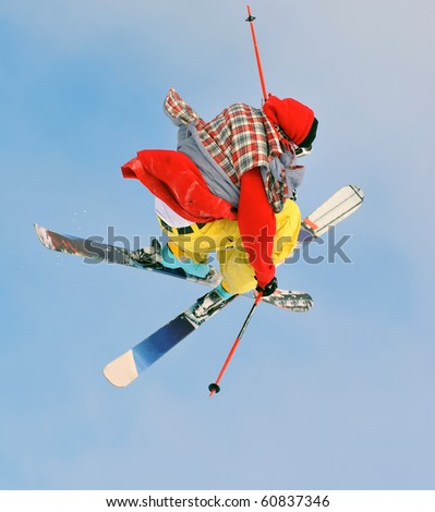 freestyle skier in bright colours performs a high jump - stock photo