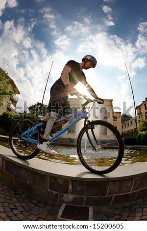 Freestyle young male rider, back-light, urban area. Fish-eye lens. - stock photo