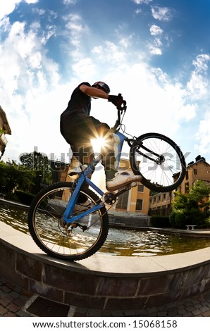 Freestyle young male rider performing a jump, urban area. Fish-eye lens. - stock photo