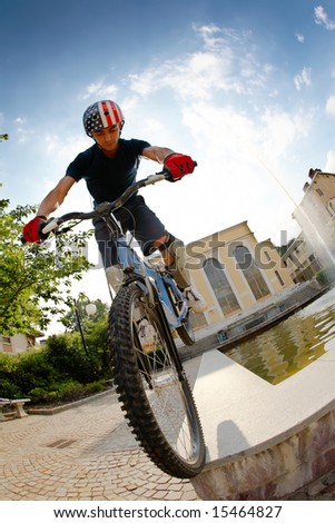Freestyle young male rider, urban location. Fish-eye lens. - stock photo
