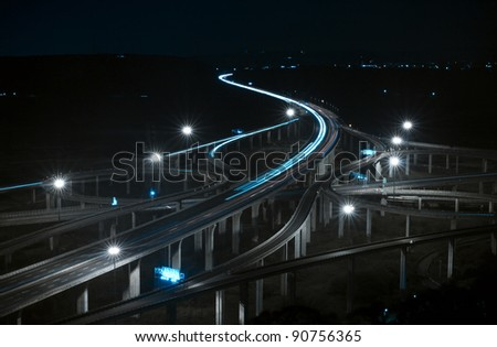 Freeway in night with cars light motion blur - stock photo