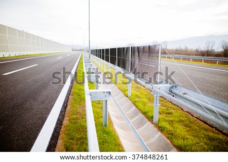 Freeway on a sunny day trough scenic green meadows.Motorway traveling long distance.Asphalt highways road in rural scene use land transport and traveling concept.Vehicular traffic.Fence.Highway bumper - stock photo