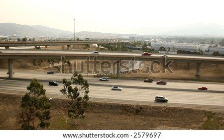 Freeway Overpass With Traffic Traveling on Smoggy Day - stock photo