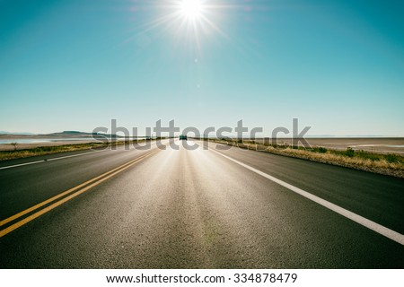 Freeway / road in the desert - at the horizon a car speeds up - stock photo
